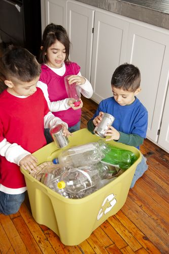 Hispanic siblings recycling together.
