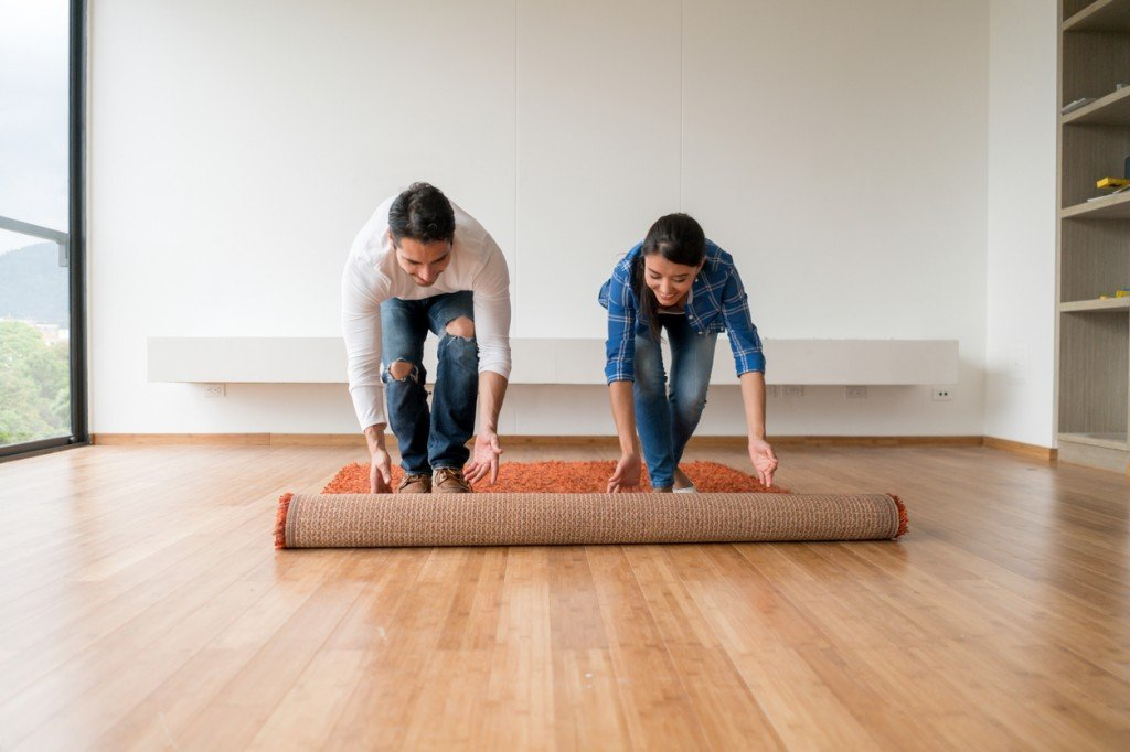 Couple unrolling a rug onto their new bamboo flooring