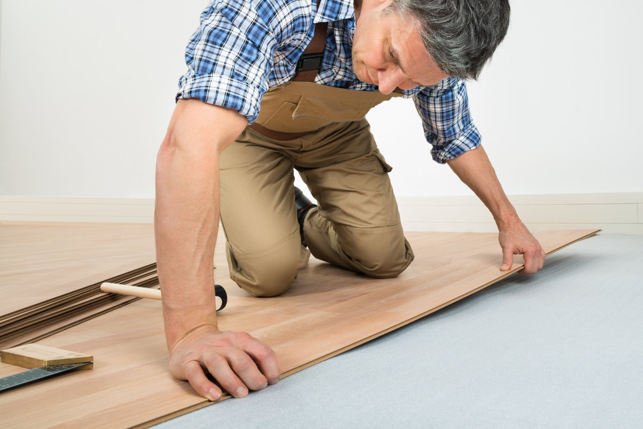 Carpenter installing new bamboo floor in a home