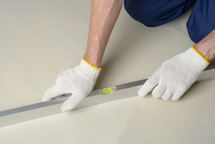 Construction worker measures the quality of floor using spirit level