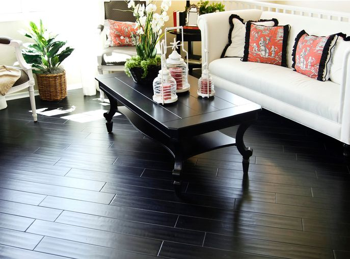 Beautiful brightly lit living room area with gorgeous dark hard wood flooring laid in a diagonal direction