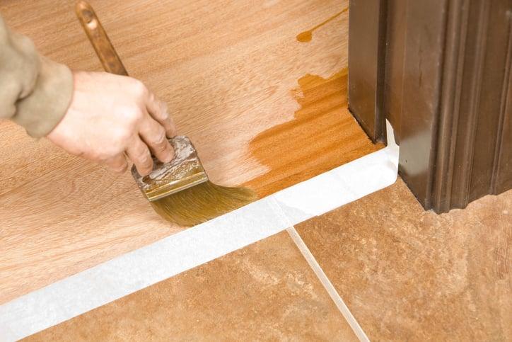 Painter Brushing Clear Polyurethane staining on Hardwood Floor