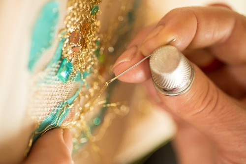 Close up shot of a ladies hands wearing a thimble and doing embroidery with gold thread and sequins