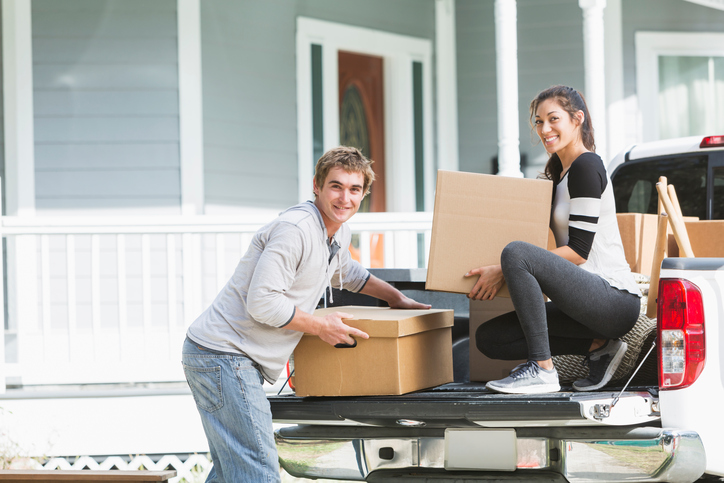 A young couple moving into a house or apartment. Their pickup truck is full of cardboard boxes and furniture. They are smiling at the camera, lifting the boxes.