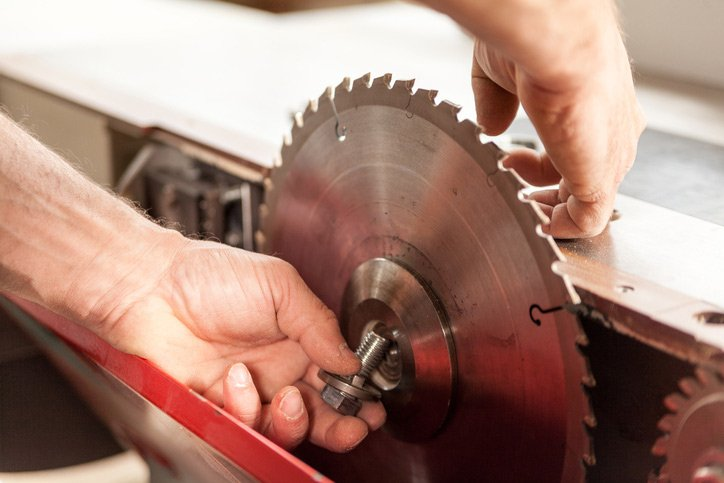 Hands of a woodworker changing a saw blade to trim bamboo flooring