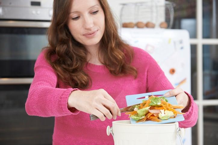 Woman Scraping Vegetable Peelings Into composting bin