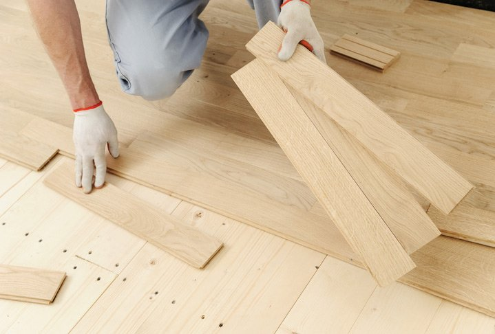 Laying hardwood parquet. Worker decides the direction and fixes the boards one by one.